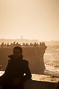 Silhouettes of people standing at coast and enjoying sea view at sunset on Corniche west of Hassan II Mosque, Casablanca, Morocco