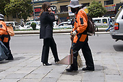 Bolivia 2010. Female street sweeper with dustpan made from recycled oil tin and female city worker talking on her mobile phone.