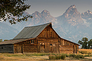 Morning sunrise over the T.A Moulton barn in the Mormon Row Historic District along Antelope Flats with the Grand Teton mountains behind at Grand Teton National Park, Wyoming.
