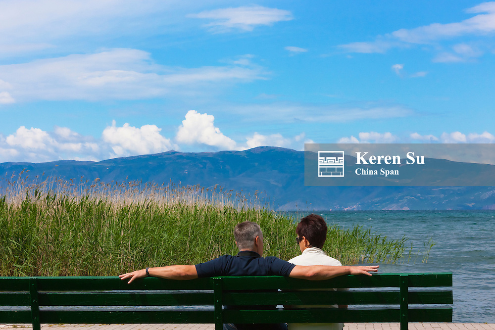 Tourists sitting on a bench by Lake Ohrid, UNESCO World Heritage site, Republic of Macedonia