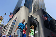 American consumers pass the tall doorway of the East River Savings Bank in Lower Manhattan, New York City. Walking across Church Street they go beneath two American flags of the bank at the corner of 26 Cortlandt Street. Seen from a low angle, we look upwards to a tall skyscraper that rises into the Manhattan sky, adjacent to the site of the former Twin Towers and Ground Zero. As US citizens, they symbolise a wealthy country whose people largely enjoy a prosperity and stability of both economy and government.
