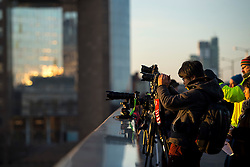 © Licensed to London News Pictures. 16/02/2016. London, UK. Photographers position themselves as the Sun rises behind Tower Bridge in central London on a cold winter morning. Temperatures in the capital dropped below zero last night. Photo credit: Ben Cawthra/LNP