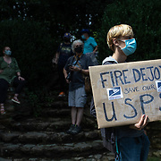 GREENSBORO, NC - August 16:  A group of protestors hold a demonstration in front of Postmaster General Louis DeJoy's home in Greensboro, NC on August 16, 2020.  DeJoy has recently come under fire for what's perceived as steps ordered by the Trump administration to slow down the United States Postal Service to help suppress absentee votes.  (Photo by Logan Cyrus for AFP)