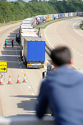 © Licensed to London News Pictures. 30/07/2015 <br /> Man watching the action from a bridge.<br /> Lorries stacked up between J8 and J9 M20 (this afternoon 30.07.2015).coast bound.<br /> Traffic misery continues on the M20 with Operation Stack and will most likely remain in place into the weekend.<br /> A 23-mile stretch of the coast-bound carriageway is shut with part of the London-bound side also closed.<br /> <br /> <br /> (Byline:Grant Falvey/LNP)