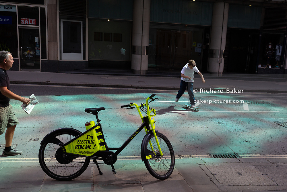 A young skateboarder makes a dash across Fenchurch Street where an electric rental Freebike stands on the pavement in reflected light, in the City of London, the capital's financial district, on 20th July 2020, in London, England.
