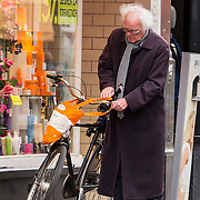 NLD/Amsterdam/20140502 - Henk Spaan op de fiets in Amsterdam,