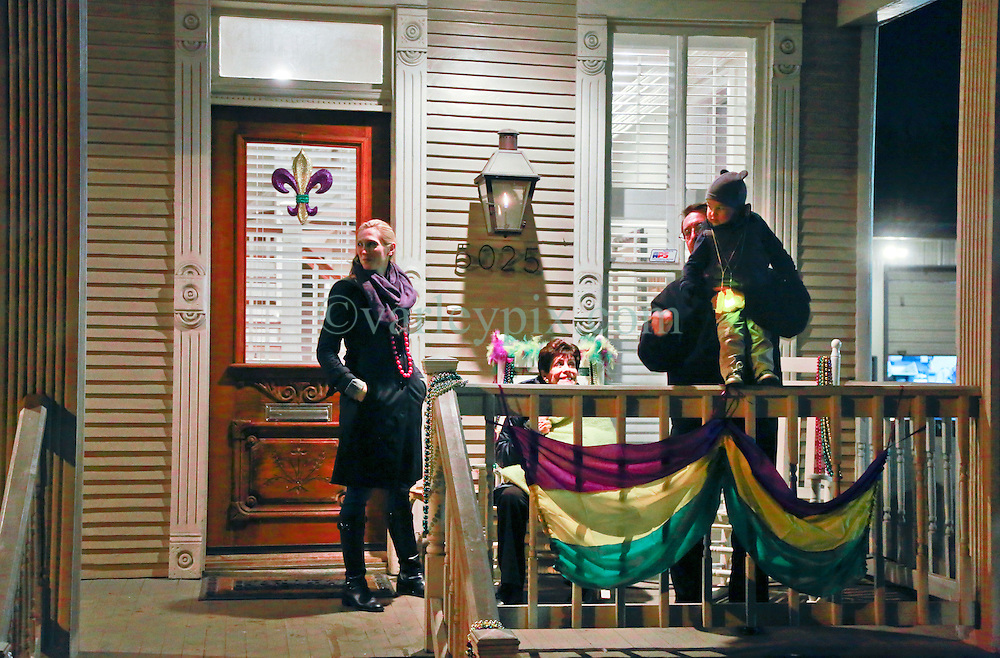 13 Feb 2015. New Orleans, Louisiana.<br /> Mardi Gras. Jackie and Xavier with friends on the front porch as Krewe D'Etat makes its way along Magazine Street.<br /> Photo; Charlie Varley/varleypix.com