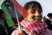 A young girl holds the flag of the independent kingdom of Libiya as Libyan exiles protest opposite their London embassy, against their long-term dictator Muammar al-Gaddafi whose violence has led to a nationwide uprising though this girl is exiled in Britain with her family. The flag of the independent kingdom was red, black, and green with a crescent and star in the centre. After the Libyan revolution of 1969, the flag was changed to the Arab Liberation Flag of horizontal red, white, and black bands. In 1971 Libya joined the Federation of Arab Republics with Egypt and Syria, which used a similar flag with a hawk emblem in the center and the name of the country beneath it. When Libya left the Federation in 1977, the new plain green flag was adopted. But during the 2011 uprising, the old flag was once again adopted.