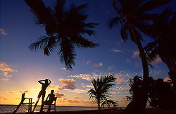 Silhouette of a couple enjoying sunset on tropical beach in Ambergris Caye, Belize.