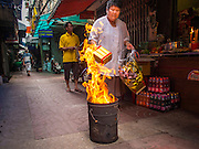 """10 AUGUST 2014 - BANGKOK, THAILAND:     A woman burns joss paper and hell money on the first day of Ghost Month in a back alley in Bangkok's Chinatown. The seventh month of the Chinese Lunar calendar is called """"Ghost Month"""" during which ghosts and spirits, including those of the deceased ancestors, come out from the lower realm. It is common for Chinese people to make merit during the month by burning """"hell money"""" and presenting food to the ghosts.  PHOTO BY JACK KURTZ"""