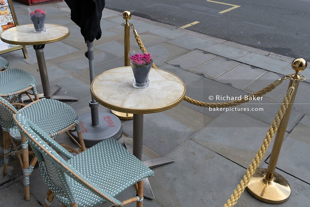 Chairs and a table with flowers are set behind a rope barrier for customers to sit outside a cafe on the street in Piccadilly during the second (Autumn) wave of the Coronavirus pandemic, on 8th October, 2020, in London, England.