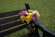 Memorial flowers left on a bench, on 22nd April 2017, in Clevedon, North Somerset, England.