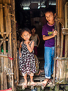 30 OCTOBER 2015 - TWANTE, MYANMAR: Children in the doorway of their home in the potters' village in Twante, (also spelled Twantay) Myanmar. Twante, about 20 miles from Yangon, is best known for its traditional pottery. The pottery makers are struggling to keep workers in their sheds though. As Myanmar opens up to outside investments and its economy expands, young people are moving to Yangon to take jobs in the better paying tourist industry or in the factories that are springing up around Yangon.     PHOTO BY JACK KURTZ
