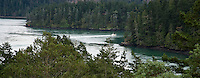 a fishing boat enters Cornet Bay from Deception Pass in Puget Sound as seen from Canoe Island. Washington, USA, panorama