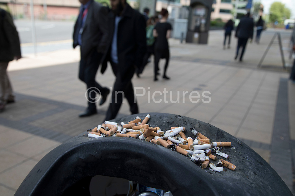 Cigarette butts on top of a bin which acts as a huge ashtray in Birmingham, United Kingdom.
