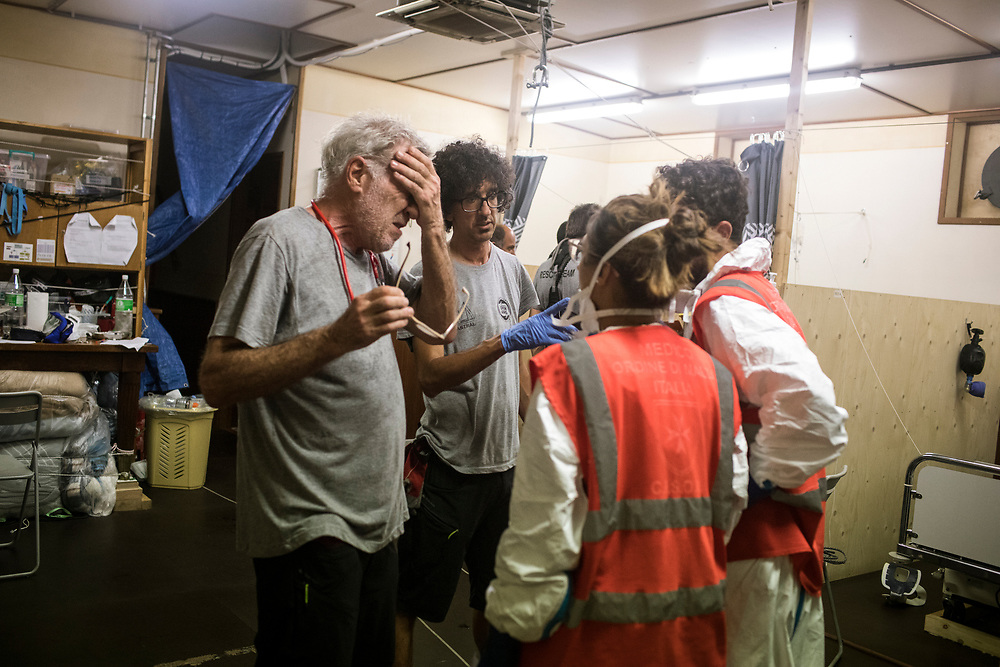 June 29th, 2017, Central Mediterranean. Doctor talking to Italian medical staff. Italian Coast Guard came to see the situation after hours and realized that they were not prepared to handel the situation. Evacuation of Samuel Osei, a 36-year-old man from Ghana severely sick after being rescued in the sea. NGO Proactiva Open Arms in their 20th rescue mission in the Central Mediterranean Sea on board of Golfo Azzurro vessel (photo Edu Bayer)