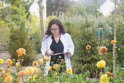 Female scientist inspecting flowers at greenhouse, Freiburg im Breisgau, Baden-Wuerttemberg, Germany