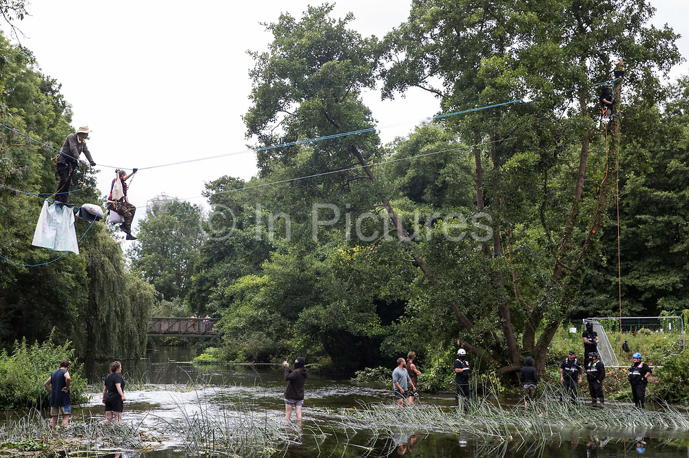 Environmental activists from HS2 Rebellion, including Larch l and Swan r on a line above the shallow river Colne in Denham Country Park, attempt to protect an ancient alder tree from destruction in connection with works for the HS2 high-speed rail link on 24th July 2020 in Denham, United Kingdom. A large security operation involving officers from the Metropolitan Police, Thames Valley Police, City of London Police and Hampshire Police as well as the National Eviction Team ensured the removal of the tree by HS2 despite the protests by activists.