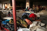 Migrants sleep on twin-sized beds at the Hotel Captain Elias in Kos, Greece on July 4, 2015. The hotel is filled with twin-sized beds wrapped in plastic placed along the floors and on plastic beach bed frames. However, not enough beds are supplied at the hotel to accommodate the numerous migrants and refugees arriving daily.