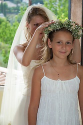 bride placing head piece on flower girl