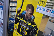 Sign advertising the computer game Cyberpunk 2077 on 29th December 2020 in Birmingham, United Kingdom. Cyberpunk 2077 is a 2020 action role-playing video game developed and published by CD Projekt. Players assume the first-person perspective of a customisable mercenary known as V, who can acquire skills in hacking and machinery with options for melee and ranged combat. Following its release it was widely criticized for bugs, particularly in the console versions which also suffered from performance issues; Sony removed it from the PlayStation Store on 17 December 2020.