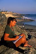 Mary Ferreta writing thoughts at beach along West Cliff Drive, Santa Cruz, CALIFORNIA