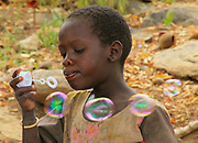 Africa, Tanzania, Lake Eyasi, young male Hadza child plays with soap bubbles. Hadza, or Hadzabe, are an indigenous ethnic group in north-central Tanzania, living around Lake Eyasi in the central Rift Valley and in the neighboring Serengeti Plateau