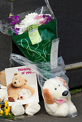 "© Licensed to London News Pictures. 27/06/2012. Oldham , UK. Flowers and a teddy bear are left by a crying couple at a makeshift shrine to two year old Jamie Heaton , who died in the exploion. The card attached to the flowers is signed off "" hugs n kisses Auntie Syl and Geoff "". A large explosion , believed to be caused by gas , has brought down at least one house in an Oldham terrace . . Photo credit : Joel Goodman/LNP"