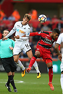 Tom Carroll of Swansea city gets to a header ahead of Elias Kachunga of Huddersfield Town. Premier league match, Swansea city v Huddersfield Town at the Liberty Stadium in Swansea, South Wales on Saturday 14th October 2017.<br /> pic by  Andrew Orchard, Andrew Orchard sports photography.