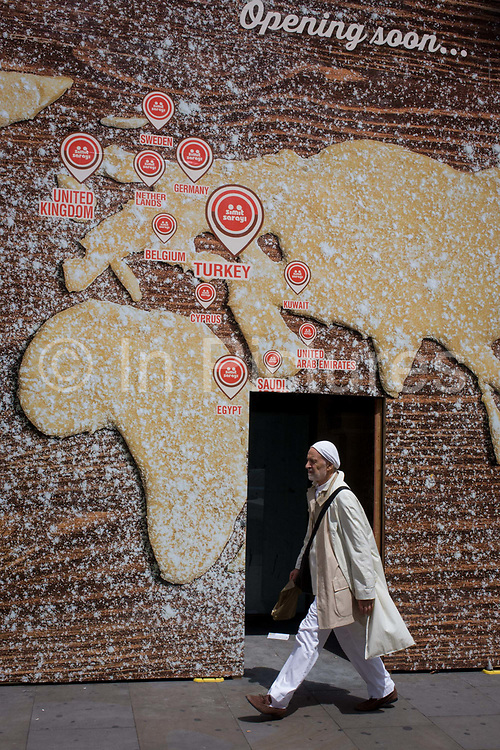 Man walks beneath a world map on a bakery business hoarding. The male passes beneath the large billboard screening off construction work for a new Turkish bagel business called Simit Sarayi that shows a world map made from dough with a dusted flour covering. Countries from America to Europe and the Middle-east show the locations of the business's presence around the globe. He walks westwards towards Piccadilly Circus. Simit Sarayı started in 2002 with a single store. Today, with hundreds of stores in Turkey and abroad with 10.000 employees to over 650.000 daily visitors.