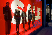 A man stands outside the entrance of a retail shop, awaiting his partner to emerge. Giant letters lure potential customers into this branch of Hobbs with a Sale offer sign. Their mannequins are seen in the window of London's Long Acre (street) clothing shop - a line-up of womens' fashion variations displayed in the window on a winter's afternoon. Further reductions are also promised if the potential customer enters the store. With an economic recession taking hold on Britain's high streets and exclusive retail outlets, deals and offers are vital to keep spending and turnover up.