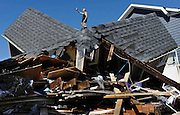 Tom Chase waves atop of his friend's beach home in the aftermath of Hurricane Irene, in East Haven, Conn. (AP Photo/Jessica Hill)