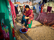 04 MARCH 2017 - KATHMANDU, NEPAL: A woman hangs her laundry in an IDP camp in the center of Kathmandu. The camp opened days after the April 2015 earthquake devastated Nepal, killing almost 9,000 people. At its peak, about 1,800 families lived in the camp. The camp is still open nearly two years after the earthquake, about 400 families currently live in the camp. Camp residents say the Kathmandu municipal government is trying to close the camp and is encouraging residents to find new housing. They said the government is cutting off services to the camp and last week stopped the free distribution of water, although water can be purchased for delivery. Most of the people in the camp came to Kathmandu from rural villages in the mountains in the weeks after the earthquake. Many of the residents of the camp, technically homeless, have found work in Kathmandu's bustling construction industry, rebuilding homes destroyed in the earthquake.       PHOTO BY JACK KURTZ