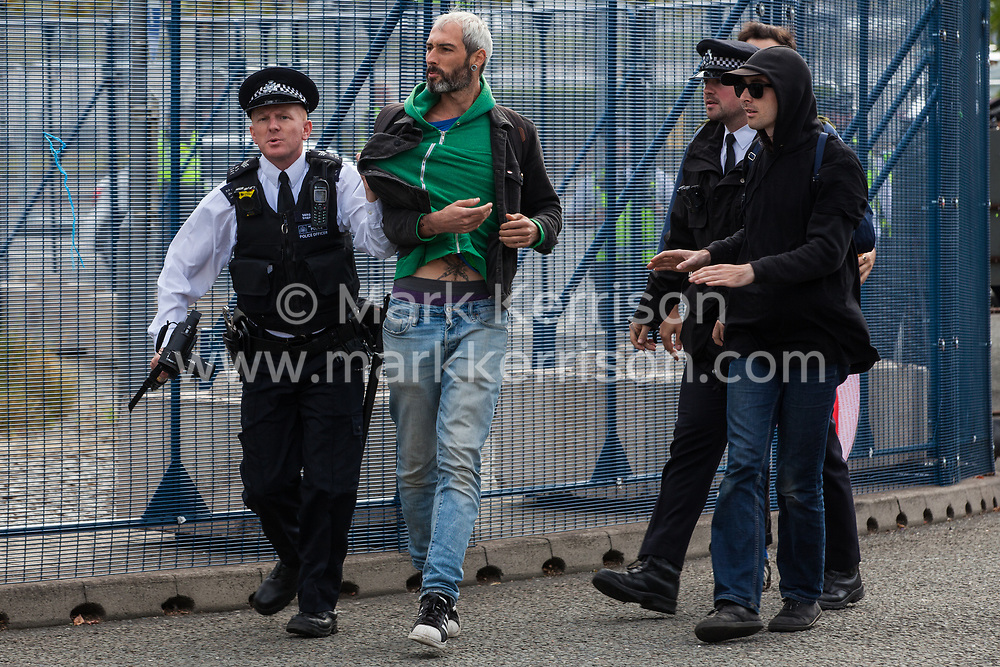 London, UK. 7 September, 2019. Metropolitan Police officers remove activists from the road in front of a truck attempting to deliver to ExCel London during the sixth day of Stop The Arms Fair protests against DSEI, the world's largest arms fair.
