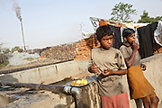 Two labourers having a meal of boiled potatoes before beginning their daily work in one of the illegal dumping and burning grounds surrounding the area of Jajmau, Kanpur, Uttar Pradesh. After being bathed in chromium and other chemicals to remove hair and impurities in a process called liming, the skins are examined by hand and the useless parts are cut and sent to one of these fields where they are boiled and reduced to a thin black dust. The resulting dark powder will then be used as a fertiliser or for the first stage of poultry food production.