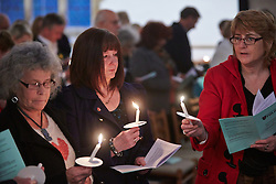 © Licensed to London News Pictures.  17/11/2013. THAME, UK. Members of the congregation light candles using a flame taken from the paschal candle during the annual Road Deaths Memorial Service held in St Marys Church, Thame. 78 people were killed in traffic accidents in the Thames Valley Police area last year.   Photo credit: Cliff Hide/LNP