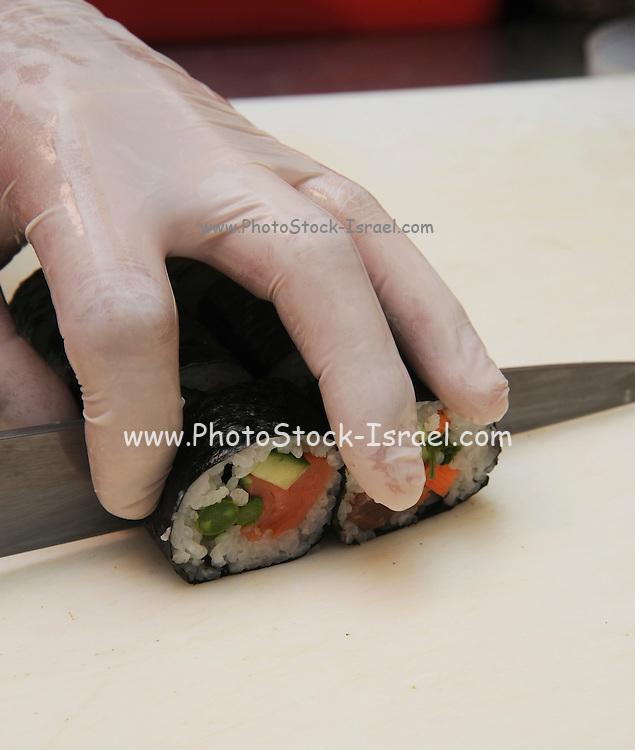 Chef cutting Sushi rolls