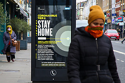 """© Licensed to London News Pictures. 29/12/2020. London, UK. Women wearing face coverings in north London walk past the government's 'Coronavirus Tier 4 - Stay Home' publicity campaign poster. Many parts of the UK entered the highest level of COVID-19 restrictions on Boxing Day after the mutated SARS-Cov-2 virus continues to spread around the country. The Medicines and Healthcare Products Regulatory Agency (MHRA) is likely to approve a COVID-19 vaccine developed by Oxford University and AstraZeneca this week.  Medical experts have warned that urgent national action is needed to prevent a """"catastrophe"""" amid rising rate of coronavirus infection, as hospitals in England are dealing with more COVID-19 patients than during the April peak. Photo credit: Dinendra Haria/LNP"""