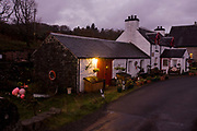 The Old Smithy (now a bed and breakfast cottage) at Pennyghael, Isle of Mull, Scotland. A night light still shines across a wet road road, a single-track highway that crosses the Ross of Mull on the southern edge of the Isle in the Inner Hebredes. (http://www.explore-isle-of-mull.co.uk/smithy-house/index.htm)