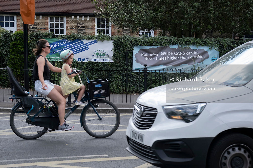 A woman cyclist carrying a child on her bike passes a pollution awareness banner that is attached to the railings of Dulwich Hamlet School, where restrictions also prevent traffic from passing through at morning and afternoon rush-hour times in the borough of Southwark, on 14th June 2021, in London, England.
