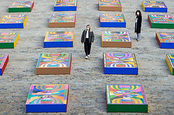 © Licensed to London News Pictures. 14/10/2021. LONDON, UK. Staff members walk amongst Lakwena Maciver's Basketball Court paintings in the courtyard of Somerset House. Preview of 1-54 Contemporary African Art Fair, the leading international art fair dedicated to contemporary art from Africa and its diaspora.  Works by around 48 exhibitors are on show in a show which runs 14 to 17 October at Somerset House.  Photo credit: Stephen Chung/LNP
