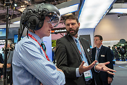 © Licensed to London News Pictures. 10/09/2019. London, UK. A visitor to DESI try's a flight helmet on as a salesman explains it's uses. Defence & Security Equipment International (DESI) is the worlds largest arms fair and is held every two years in London. Photo credit: Peter Manning/LNP