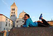 Child (9 years old), laying on wall, Church of St. Mary (Crkva Sveti Marije) in background, in late afternoon sunlight. Zadar, Croatia