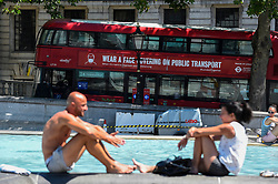 © Licensed to London News Pictures. 25/06/2020. LONDON, UK.  Tourists enjoy the sunshine in Trafalgar Square, on what is forecast to be the hottest day of the year so far.  The Met Office's UV index is expected to reach exceptionally high levels, due to clear skies and an absence of aircraft vapour trails due to a reduction in flights during the coronavirus pandemic..  Photo credit: Stephen Chung/LNP
