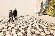 """New York, NY - May 3, 2019. Spectators wander through Yayoi Kusame's """"Narcissus Garden"""" full of stainless steel spheres, in front of Chris Olifi's oil """"to take and to give"""" in the Victoria Miro Gallery at the Frieze Art Fair on New York City's Randalls Island."""