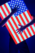 Blacklight photo of a man's arms hugging a glowing American flag.