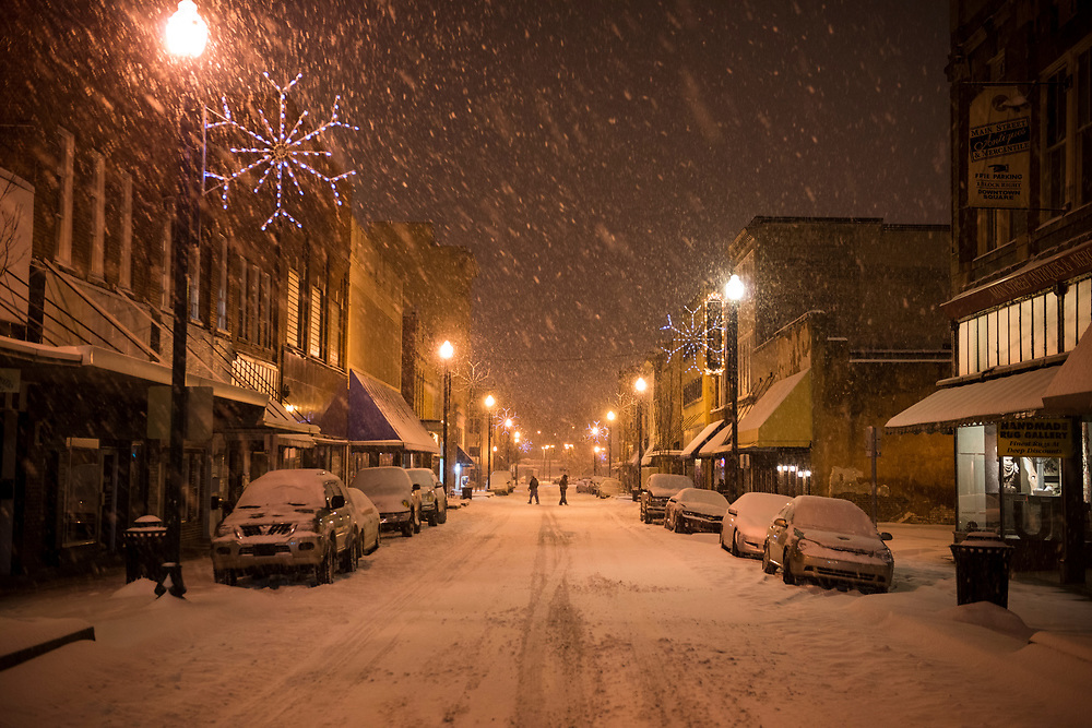 Heavy snow falls on E Main Street at 10.24 p.m. in downtown Johnson City, Tennessee. Two people are crossing the street in the background. (February 12, 2014)