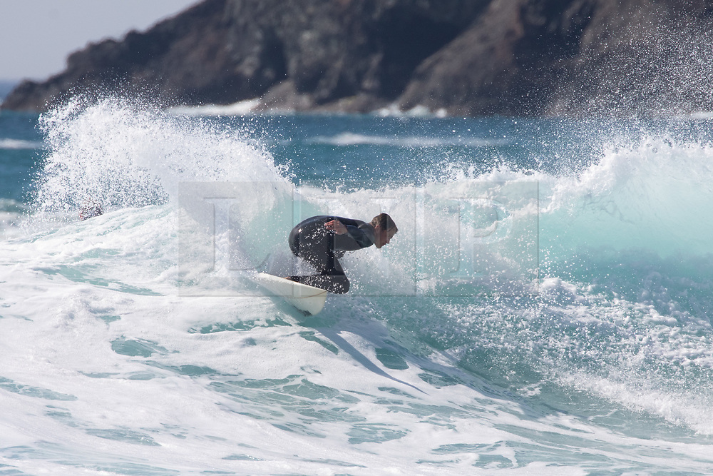 © Licensed to London News Pictures. 20/05/2020. Padstow, UK. A surfer catches a wave at Constantine Bay on the north coast of Cornwall during hot weather. The weather in the south-west is forecast to be warm for the following week. Photo credit : Tom Nicholson/LNP