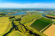 Nederland, Noord-Brabant, Werkendam, 23-08-2016; Ruimte voor de Rivier project Ontpoldering Noordwaard. Foto richting rivier de Nieuwe Merwede en Werkendam. De bandijk (winterdijk) is voorzien van doorlaten annex brug, boerderijen zijn op terpen gebouwd. De dijken aan de rivierzijde zijn gedeeltelijk afgegraven waardoor rivier de Nieuwe Merwede bij hoogwater via de Noordwaard en de Biesbosch sneller naar zee stromen. Gevolg van de ingrepen is dat de waterstand verder stroomopwaarts zal dalen. Ook de getijden keren terug in het gebied.<br /> National Project Ruimte voor de Rivier (Room for the River) By lowering and moving the dike of the Noordwaard polder the area will become subject to controlled inundation and function as a dedicated water detention district. Houses and farmhouses havbeen demolished and rebuild  on new dwelling mounds.<br /> luchtfoto (toeslag op standard tarieven);<br /> aerial photo (additional fee required);<br /> copyright foto/photo Siebe Swart