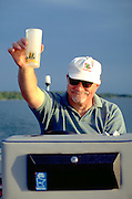 Man age 55 holding up drink while driving motor boat.  Clitherall  Minnesota USA